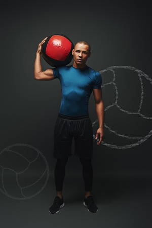 Full length shot of a crossfit male athlete working out with exercise ball. Handsome muscular athletic sportsman exercising with the ball over dark background in studio. Endurance concept. Graphic drawing.