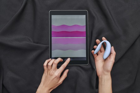 How to use? Top view of female hands holding blue g-spot vibrator and digital tablet against of black silk.