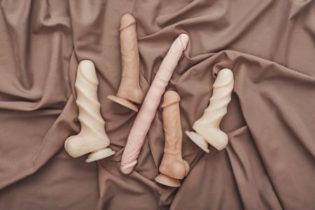 Double your pleasure! Different realistic dildos in various size arranged on a beige silk fabric.