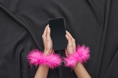She is in your control. Female hands in pink furry handcuffs holding smartphone on a black silk fabric Stock Photo - 118549851
