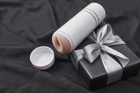 Regalo giocattolo sessuale per l'uomo che ami! Foto ravvicinata del masturbatore maschile e della confezione regalo disposti su un tessuto di seta nera