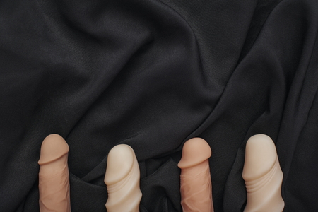 Double your pleasure! Composition of various realistic dildos arranged on a black silk fabric. Sex toys.