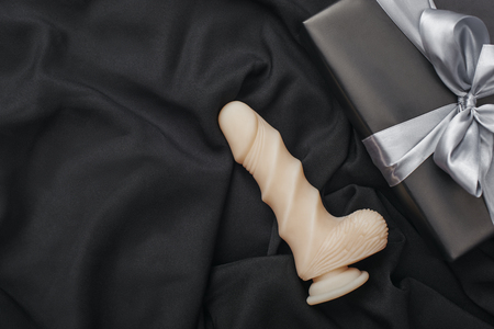 Sex toy gift for the women you love! Close up photo of natural-looking dildo and black gift box Reklamní fotografie