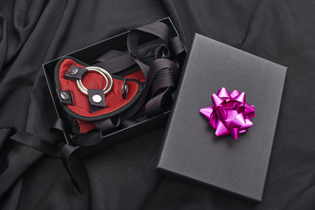 Ideal Bdsm Gift. Close up photo of a gift box with bdsm stuff laying on a black silk Stock Photo
