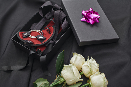 Valentines Day gift ideas. Close up photo of a gift box with bdsm stuff and fresh white roses laying on a black silk. Erotic toys. Gifts for adults
