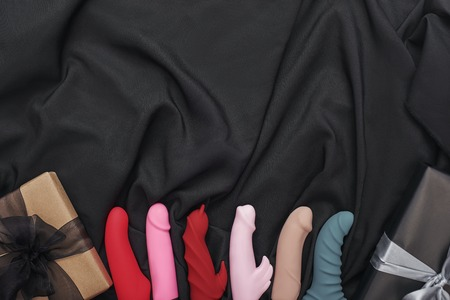 Adult Toys for Sexual Pleasure. Composition of various colorful dildos with gift boxes arranged on black silk. Adult gifts. Sex toys.
