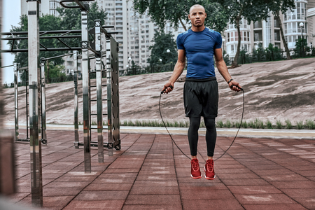 Muscular african man is skipping rope. Portrait of muscular young man exercising