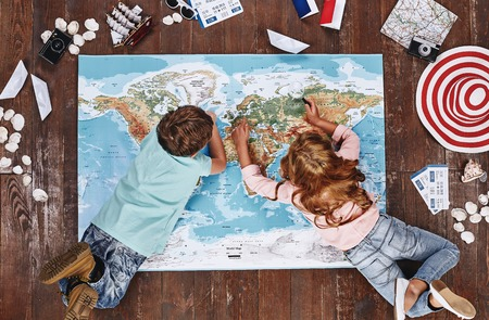 Where would you like to visit Children looking at world map, while lying on it, near travel items