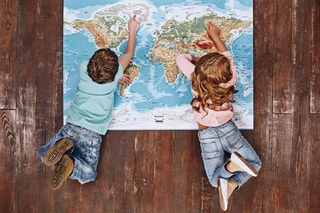 Discover the World. Children lying on world map, looking at it