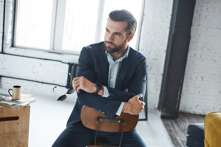 Handsome bearded businessman is sitting on the chair at office and thinking about something
