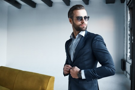 Young stylish businessman leader indoors at office wearing sunglasses looking aside thoughtful