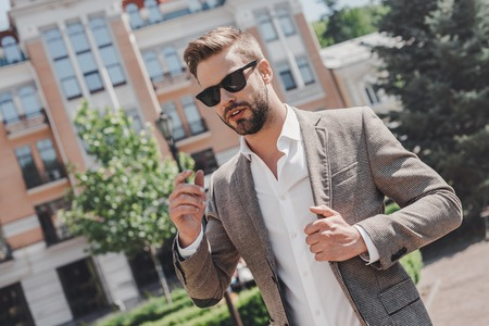 Live each day as if your life had just begun. Portrait of brown-haired man wearing sunglasses and looking away in the city streets. Zdjęcie Seryjne