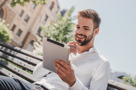 Social life. Young smiling man sitting on a bench in the park, holding his tablet. Rest, communication and relax concept