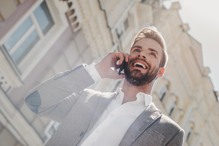Dream bigger. Do bigger. Young businessman talking on smartphone. Casual urban professional businessman using mobile cell phone smiling happily while walking. Imagens