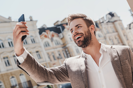 Do something today that your future self will thank you for. Smiling brown-haired man standing outdoors and using his smartphone. He holds his phone against his head