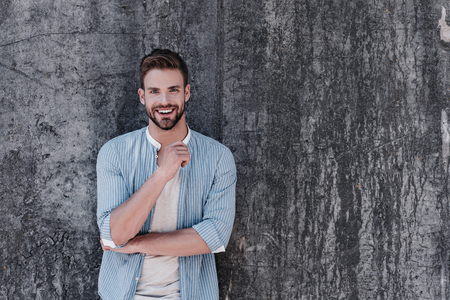 Self-belief and hard work will always earn you success. Smiling brown-haired man with blue eyes standing isolated over grey background 写真素材