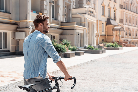 I am a slow walker, but I never walk back.Young brown-haired man standing outdoors with a bicycle and looking away.
