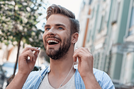 Music is an outburst of the soul. Young man is listening to music via earphones while walking around the city Stock fotó
