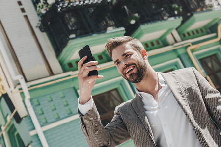Im only in the mood for good news today. Smiling brown-haired man standing outdoors and using his smartphone. He holds his phone against his head Banco de Imagens