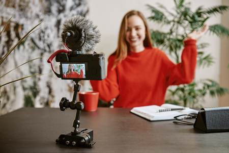 I want your likes! Portrait of cheerful young broadcasting a new tutorial for her vlog with tripod mounted digital camera