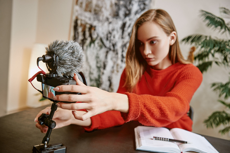 Im almost ready... Portrait of serious female blogger setting up her tripod mounted digital camera before making a new video for vlog Stock Photo