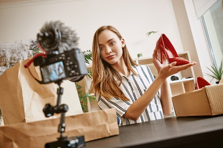 Red shoes. Beautiful female fashion blogger talking about trendy footwear while making a video for her blog.
