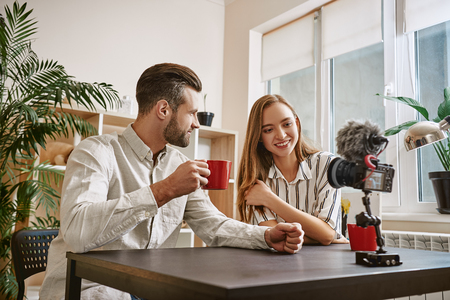 Successful bloggers. Smiling bloggers drinking a tea while making new content for their blog