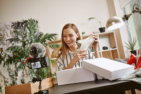 Creating content. Beautiful female fashion blogger talking about trendy white sneakers while making a video for her blog. Stock Photo