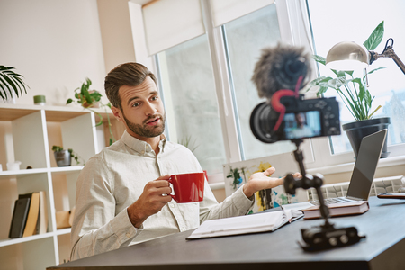 Creating content. Cheerful male blogger making a new video for his vlog and drinking a tea while sitting indoors.