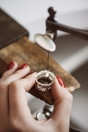Skillful work. Close up of a female jewelers hand working on a ring resizing at her workbench. Ring Resizing. Banque d'images