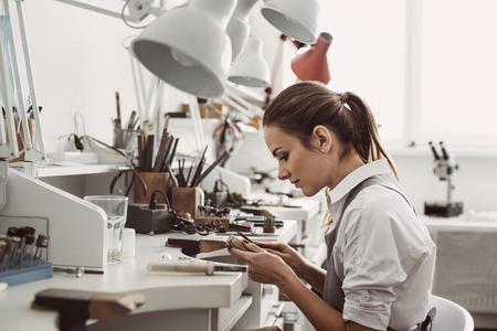 Trabajando todo el dia. Vista lateral de la joven joyero sentado en su taller de joyería y sosteniendo en las manos herramientas de joyería para hacer accesorios Foto de archivo