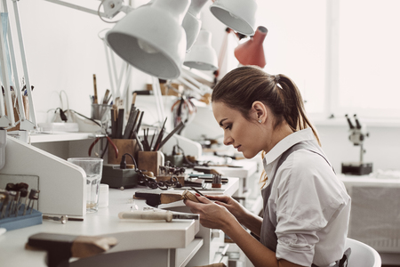 Working all day. Side view of young female jeweler sitting at her jewelry workshop and holding in hands jewelry tools for making accessories Stock Photo