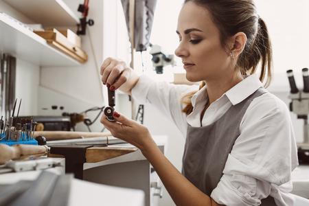 Sie weiß, was sie tut. Seitenansicht der jungen Juwelierin, die die Werkzeuge für die Schmuckherstellung vorbereitet.