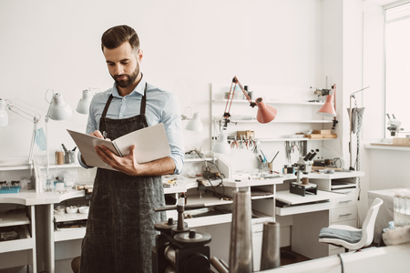 Report preparation. Portrait of bearded male jeweler in apron planning a day in notebook