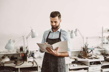 Working. Portrait of young male jeweler in apron writing in notebook