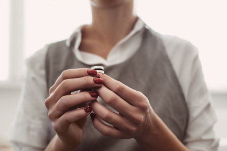Ideal work. Portrait of female jewelers hands examining the silver ring at workshop.