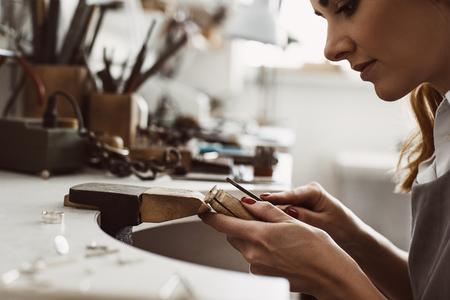 Tengo mi inspiración. Vista lateral de una mujer joyero emocionado creando un anillo de plata en su banco de trabajo. Hacer accesorios