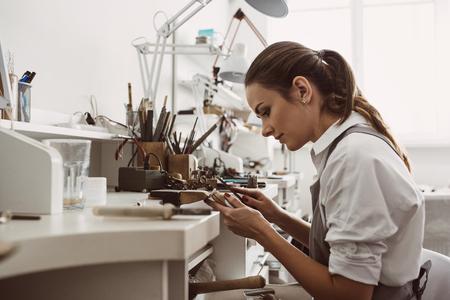 Centrado en un proceso. Retrato de joven joyero centrado en la creación de un anillo de plata en su moderno banco de trabajo.