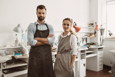 Business for a couple. Portrait of smiling couple in aprons standing at their jewelry workshop and looking at camera