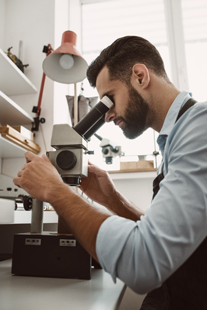 Maximum accuracy. Side view of a male jeweler looking at the ring through microscope in a workshop.