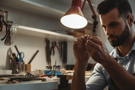 Perfection. Close up of young male jeweler looking and inspecting a ring.