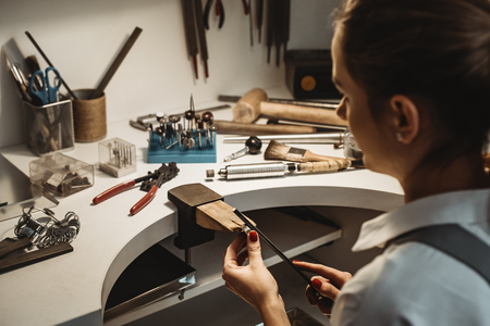 Focused on a process. Back view of a female jeweler working and shaping an unfinished ring with a tool at workbench in workshop. Stock Photo