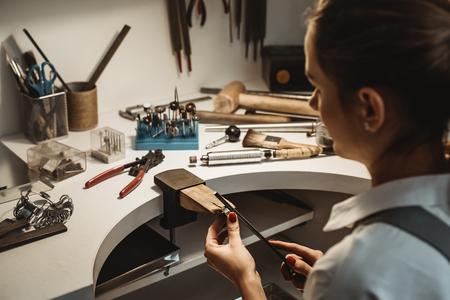Gericht op een proces. Achteraanzicht van een vrouwelijke juwelier die een onvoltooide ring bewerkt en vormgeeft met een gereedschap op de werkbank in de werkplaats. Stockfoto