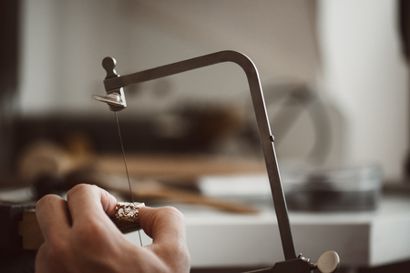 I know what i am doing. Close-up photo of jewelers hands making a silver ring with professional adjustable jewelers saw frame Banco de Imagens