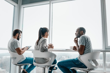 Multi-cultural colleagues are joking during coffee break at workplace