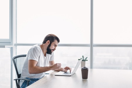 Portrait of dark-haired businessman with beard speaking on his smartphone while working on a laptop at his desk. Side view Stock Photo