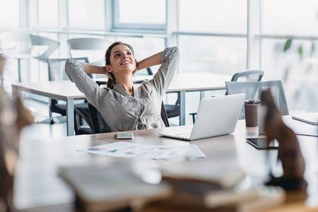 Glückliche Geschäftsfrau, die sich mit den Händen hinter dem Kopf am Schreibtisch entspannt. Tagtraumkonzept