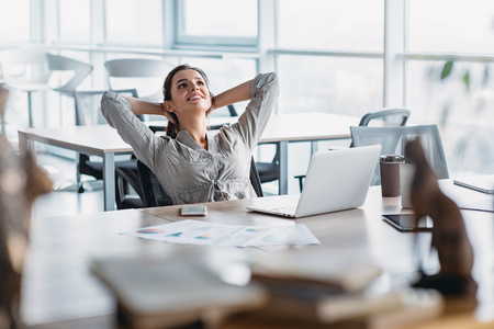 Happy businesswoman relaxing with hands behind head at office desk. Daydreaming concept Imagens - 117688870