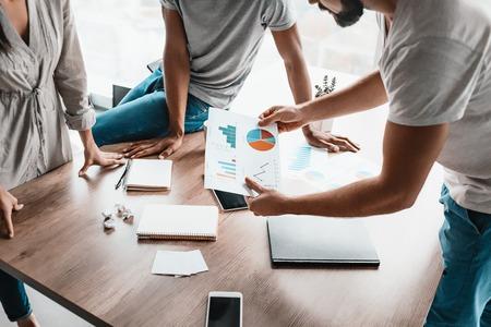 Cerca de la mesa de oficina de madera. Análisis de grupo de jóvenes empresarios al gráfico de papel de datos en el escritorio en el espacio de trabajo.