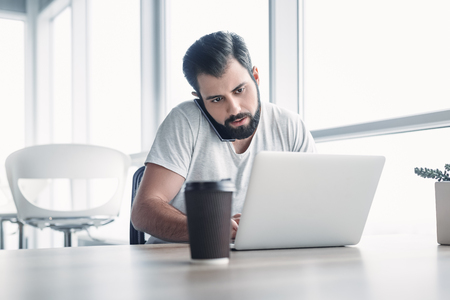 Portrait of dark-haired businessman with beard speaking on his smartphone while working on a laptop at his desk.